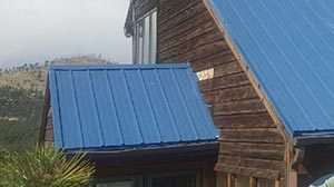 a house in the mountains with a blue metal roof