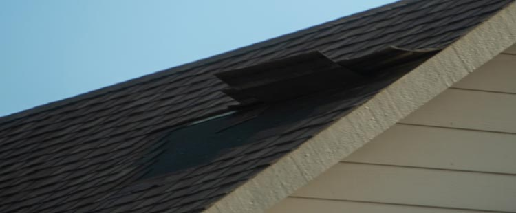 asphalt shingle roof with wind damage, missing shingles